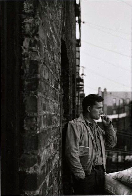 "Original photographic portrait of Jack Kerouac, 11 x 7 inches (image size), inscribed in the margin below the image: ""Jack Kerouac, classic portrait with brakeman's manual in jacket pocket, on my fire-escape 206 East 7Street N.Y.C. Fall 1953 Allen Ginsberg"""